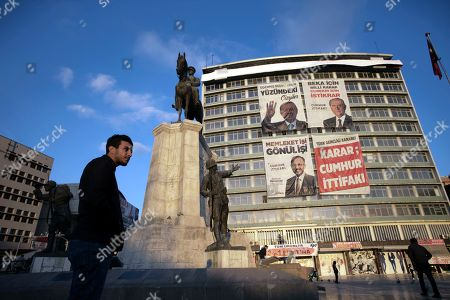 Stock Photo of An unemployed man stands next to a statue depicting Turkey's War of Independence in old part of Turkish capital, Ankara, Turkey, . A poster with images of Turkey's President Recep Tayyip Erdogan, top left, Devlet Bahceli, leader of the opposition Nationalist Movement Party, MHP, top right, and Mehmet Ozhaseki, the mayoral candidate for Ankara of Erdogan's ruling Justice and Development Party, AKP, and MHP is in the background, ahead of local elections scheduled for March 31, 2019