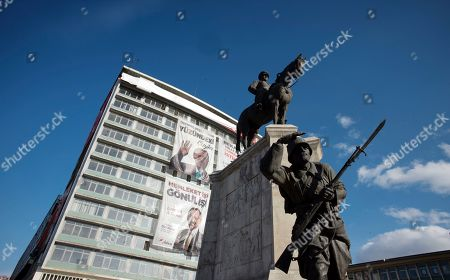 A statue depicting Turkey's War of Independence in old part of Turkish capital, Ankara, Turkey, . A poster with images of Turkey's President Recep Tayyip Erdogan, top left, Devlet Bahceli, leader of the opposition Nationalist Movement Party, MHP, top right, and Mehmet Ozhaseki, the mayoral candidate for Ankara of Erdogan's ruling Justice and Development Party, AKP, and MHP is in the background, ahead of local elections scheduled for March 31, 2019