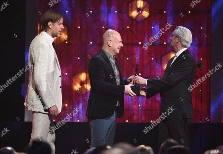 David Byrne, Philip Selway, Ed O'Brien. David Byrne, from right, presents a trophy to inductees Philip Selway and Ed O'Brien, of Radiohead, at the Rock & Roll Hall of Fame induction ceremony at the Barclays Center, in New York