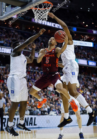 Justin Robinson, Zion Williamson. Virginia Tech guard Justin Robinson (5) drives to the basket between Duke forward Zion Williamson (1) and center Marques Bolden during the second half of an NCAA men's college basketball tournament East Region semifinal in Washington