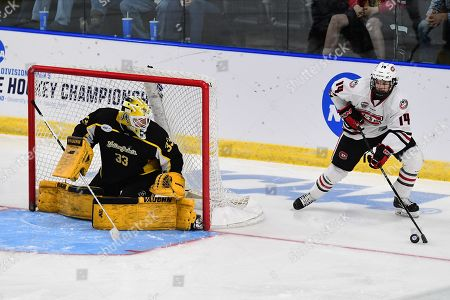 St. Cloud State Huskies forward Patrick Newell (14) brings the puck from behind the net as American International Yellow Jackets goaltender Zackarias Skog (33) keeps and eye on him during the NCAA Men's Hockey West Regional semi-final game between the American International College Yellow Jackets and the St. Cloud State Huskies at Scheels Arena, Fargo, ND. #16 AIC defeated #1 SCSU 2-1