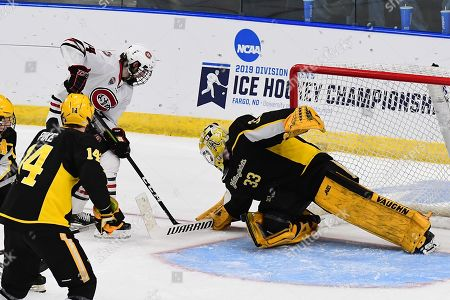 Stock Image of St. Cloud State Huskies forward Patrick Newell (14) shoots on American International Yellow Jackets goaltender Zackarias Skog (33) during the NCAA Men's Hockey West Regional semi-final game between the American International College Yellow Jackets and the St. Cloud State Huskies at Scheels Arena, Fargo, ND. #16 AIC defeated #1 SCSU 2-1