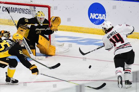 St. Cloud State Huskies forward Patrick Newell (14) shoots on American International Yellow Jackets goaltender Zackarias Skog (33) during the NCAA Men's Hockey West Regional semi-final game between the American International College Yellow Jackets and the St. Cloud State Huskies at Scheels Arena, Fargo, ND. #16 AIC defeated #1 SCSU 2-1