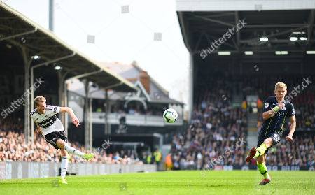 Andre Schurrle of Fulham crosses past Oleksandr Zinchenko of Manchester City