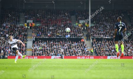 Andre Schurrle of Fulham takes a free kick as Raheem Sterling of Manchester City jumps