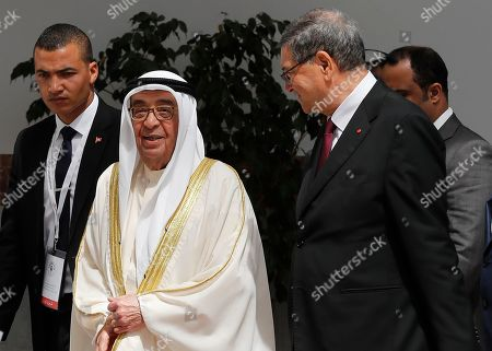 Bahrain's deputy prime minister, Sheikh Mohammad bin Mubarak al-Khalifa, center, who will represent his country on the Arab Summit, speaks with the Tunisian Presidential Advisor for political affairs, Habib Essid, right, upon his arrival at Tunis-Carthage international airport, in Tunis, Tunisia