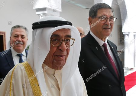 Bahrain's deputy prime minister, Sheikh Mohammad bin Mubarak al-Khalifa, center, who will represent his country on the Arab Summit, walks next of the Tunisian Presidential Advisor for political affairs, Habib Essid, right, upon his arrival at Tunis-Carthage international airport, in Tunis, Tunisia