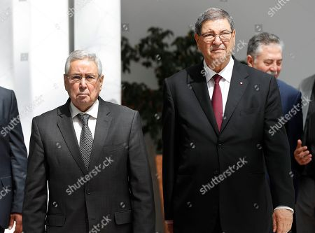 Algerian Speaker of the National Assembly Abdulkader bin Saleh, left, who will represent his country on the Arab Summit, walks next to Tunisian Presidential Advisor for political affairs, Habib Essid, right, upon his arrival at Tunis-Carthage international airport to attend the Arab Summit, in Tunis, Tunisia, . Arab leaders meeting in Tunisia on Sunday hope to project unified opposition to the Trump administration's acceptance of Israeli control over the Golan Heights and Jerusalem, but as with past Arab League summits, the gathering is likely to expose their own bitter rivalries