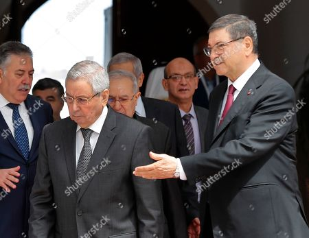 Algerian Speaker of the National Assembly Abdulkader bin Saleh, left, who will represent his country on the Arab Summit, is welcomed by the Tunisian Presidential Advisor for political affairs, Habib Essid, right, upon his arrival at Tunis-Carthage international airport to attend the Arab Summit, in Tunis, Tunisia