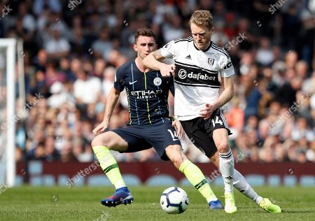 Fulham's Andre Schurrle controls the ball in front of Manchester City's Aymeric Laporte, left, during the English Premier League soccer match between Fulham and Manchester City at Craven Cottage stadium in London