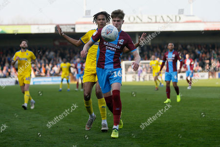 Scunthorpe United defender Tom Pearce (16) shields the ball from Wimbledon defender Toby Sibbick (20)  during the EFL Sky Bet League 1 match between Scunthorpe United and AFC Wimbledon at Glanford Park, Scunthorpe