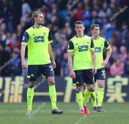 Jon Gorenc-Stankovic  ,  Erik Durm and  Jonathan Hogg of Huddersfield  of Huddersfield dejected after their team is being relegated