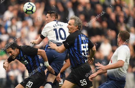 Robbie Keane of Spurs Legends leaps for the ball between Fabio Galante of Inter Forever and Laurent Blanc of Inter Forever