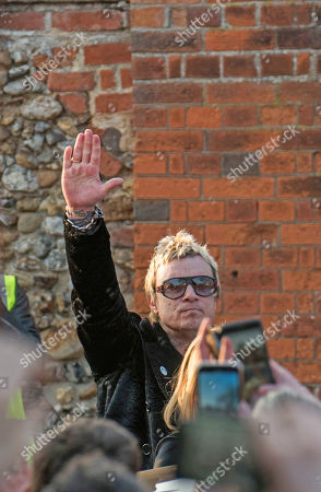 Stock Photo of Liam Howlett of the Prodigy leaves the service and salutes the lined up fans.