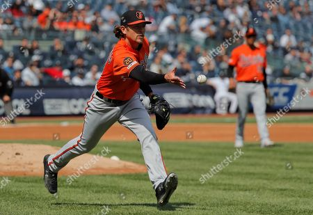 Baltimore Orioles pitcher Jimmy Yacabonis tosses the ball to first base for a force out on New York Yankees' Brett Gardner during the third inning of a baseball game, in New York. The Orioles won 5-3