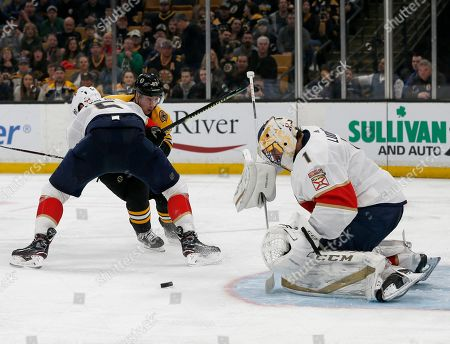 Florida Panthers goaltender Roberto Luongo (1) makes a save as defenseman Aaron Ekblad (5) blocks Boston Bruins left wing Brad Marchand (63) from the puck during the second period of an NHL hockey game, in Boston