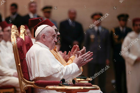 Pope Francis sits by King Mohamed VI, at the Mohammed VI Institute, a school of learning for imams, in Rabat, Morocco, . Francis's weekend trip to Morocco aims to highlight the North African nation's tradition of Christian-Muslim ties while also letting him show solidarity with migrants at Europe's door and tend to a tiny Catholic flock on the peripheries