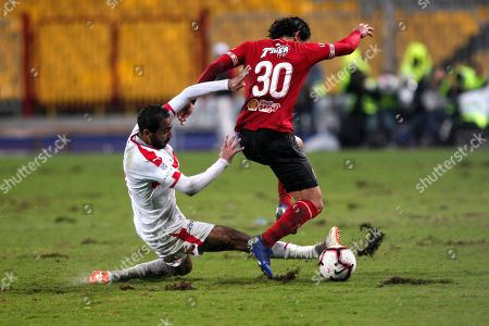Stock Image of Al-Zamalek player Mahmoud Kahraba (l) fights for the ball with Al-Ahly players Mohamed Hany  (r) and Marwan Mohsen (L)during the Egyptian Premier League soccer match between Al-Ahly and Al-Zamalek at Borg Al Arab stadium, Cairo, Egypt, 30 March 2018.