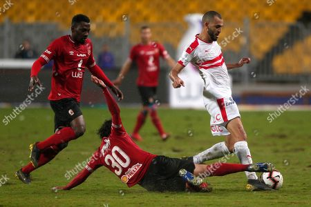 Al-Zamalek player Khaled Bou Tyeb (R) fights for the ball with Al-Ahly players Mohamed Hany  (C) and Marwan Mohsen (L)during the Egyptian Premier League soccer match between Al-Ahly and Al-Zamalek at Borg Al Arab stadium, Cairo, Egypt, 30 March 2018.