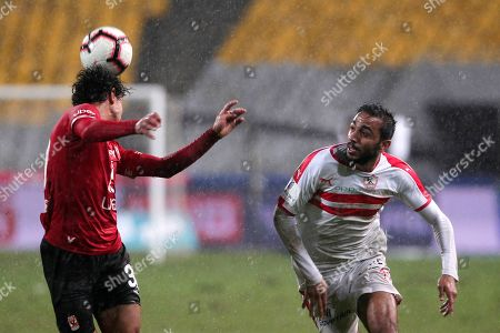 Stock Photo of Al-Zamalek player Mahmoud Kahraba (r) fights for the ball with Al-Ahly players Mohamed Hany  (l) and Marwan Mohsen (L)during the Egyptian Premier League soccer match between Al-Ahly and Al-Zamalek at Borg Al Arab stadium, Cairo, Egypt, 30 March 2018.