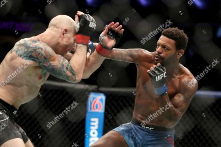 Michael Johnson, right, lands a punch against Josh Emmett during their mixed martial arts bout at UFC Fight Night, in Philadelphia. Emmett won via 3rd round KO