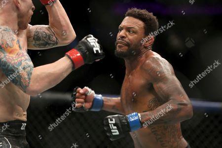Michael Johnson, right, pursues Josh Emmett during their mixed martial arts bout at UFC Fight Night, in Philadelphia. Emmett won via 3rd round KO