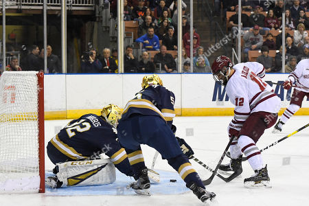 Notre Dame Fighting Irish goaltender Cale Morris (32) scrambles to cover the shot from Massachusetts Minutemen forward Anthony Del Gaizo (12) during the NCAA Northeast Regional Championship ice hockey game between the Notre Dame Fighting Irish and the Massachusetts Minutemen held at the SNHU Arena in Manchester NH