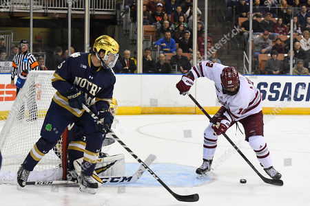 Massachusetts Minutemen forward Anthony Del Gaizo (12) lines up a shot on Notre Dame Fighting Irish goaltender Cale Morris (32) during the NCAA Northeast Regional Championship ice hockey game between the Notre Dame Fighting Irish and the Massachusetts Minutemen held at the SNHU Arena in Manchester NH