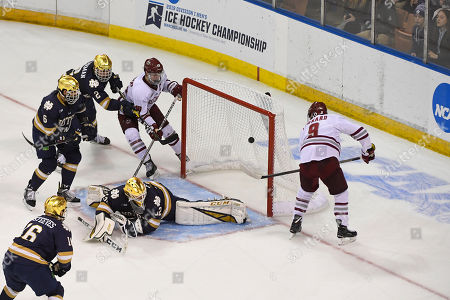 Massachusetts Minutemen forward John Leonard (9) scores against Notre Dame Fighting Irish goaltender Cale Morris (32) during the NCAA Northeast Regional Championship ice hockey game between the Notre Dame Fighting Irish and the Massachusetts Minutemen held at the SNHU Arena in Manchester NH
