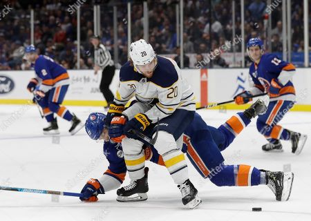 Buffalo Sabres' Scott Wilson (20) fights for control of the puck with New York Islanders' Anders Lee during the second period of an NHL hockey game, in Uniondale, N.Y