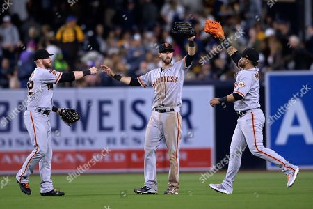 San Francisco Giants' Michael Reed, Steven Duggar and Gerardo Parra, from left, celebrate in the outfield after the Giants defeated the San Diego Padres 3-2 in a baseball game, in San Diego