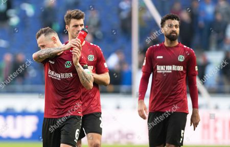 Hannover players (L-R) Marvin Bakalorz, Hendrik Weydandt, and Felipe Martins react after the German Bundesliga soccer match between Hannover 96 and FC Schalke 04 in Hanover, Germany, 31 March 2019.