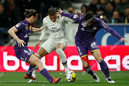 Paris Saint Germain's Kylian Mbappe (C) and Toulouse FC's Gen Shoji (R) and Toulouse FC's Yannick Cahuzac (L) in action during the soccer ligue 1 match between Paris Saint Germain and Toulouse FC, Toulouse Southern France, 31 March 2019.