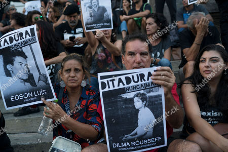 """A man hold an image of the former President Dilma Rousseff, who was tortured during the dictatorship as he takes part in a protest against the military coup of 1964 in Rio de Janeiro, Brazil, . Brazil's president Jair Bolsonaro, a former army captain who waxes nostalgic for the 1964-1985 dictatorship, asked Brazil's Defense Ministry to organize """"due commemorations"""" on March 31, the day historians say marks the coup that began the dictatorship"""