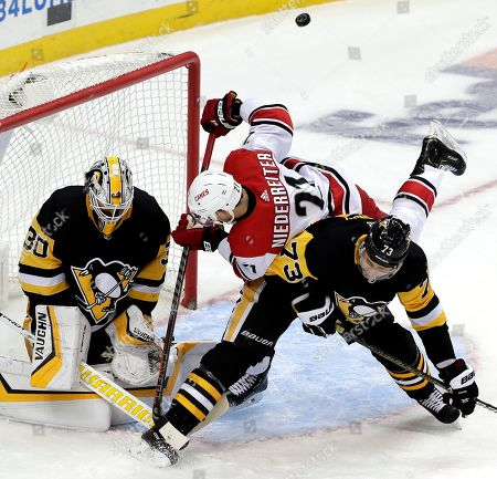Pittsburgh Penguins goaltender Matt Murray (30) blocks a shot by Carolina Hurricanes' Nino Niederreiter (21) with Jack Johnson (73) defending during the third period of an NHL hockey game in Pittsburgh, . The Penguins won 3-1
