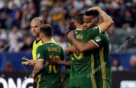 Jeremy Ebobisse, David Guzman. Portland Timbers forward Jeremy Ebobisse, right, hugs teammate David Guzman after Ebobisse's goal against the Los Angeles Galaxy during the first half of an MLS soccer match, in Carson, Calif