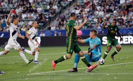 David Guzman, David Bingham, Jeremy Ebobisse. Portland Timbers midfielder David Guzman, center, passes the ball past Los Angeles Galaxy goalkeeper David Bingham, in blue, to assist on a goal by forward Jeremy Ebobisse, right, during the first half of an MLS soccer match, in Carson, Calif