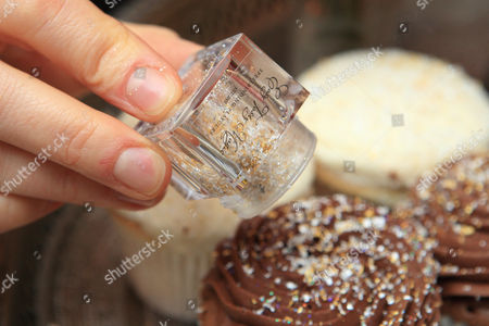 Gold and silver flakes being sprinkled on cakes.