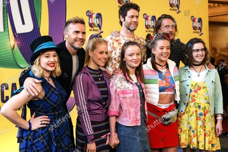 The members of the pop band Take That, Gary Barlow (L), Mark Owen (R) and Howard Donald pose for pictures with part of the cast during their visit to the rehearsals of their musical in Berlin, Germany, 01 April 2019. The event THE BAND is a jukebox musical with music and lyrics by Take That and a book by Tim Firth. It tells the story of five teenagers who were fans of Take That and, 25 years later, the women reunite to fulfill their dream of seeing the band perform.