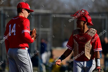 Stock Photo of Delaware State's Zach Dale (14) talks with Alex Vasquez during the sixth inning of an NCAA college baseball game at Hank DeVincent Field, in Philadelphia. La Salle defeated Delaware State 12-2
