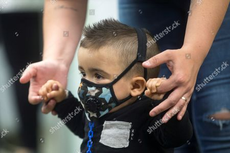 'Bubble boy' Derek poses with her mother during a press conference held on the occasion of his first medical revision after a successful umbilical cordon transplant at the Vall d'Hebron Hospital in Barcelona, northeastern Spain, 01 April 2019. Derek, one year and a month old, could undergo an umbilical cordon transplant only three months after his birth thanks to a previous diagnostic test, and he didn't suffer any infection since then. Now doctors from the Vall d'Hebron confirm that the baby has an immune system that works correctly and he may not need to wear the mask, that has prevented him from getting any infection until now, anymore. Derek is the first baby cured of a severe combined immunodeficiency (SCID), or 'Bubble Boy' disease- detected through a neonatal screening.