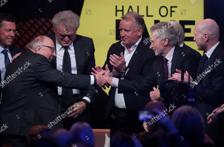 Stock Photo of German former soccer player Paul Breitner (2-R) congratulates German former soccer player Uwe Seeler (L) during the opening gala of the 'Hall Of Fame' of German football in Dortmund, Germany, 01 April 2019. The Hall Of Fame will be part of the permanent exhibition in the German Football Museum, where players and coaches of men's and women's soccer of German origin will be honored for their outstanding achievements in shaping German soccer from 1900 until today.