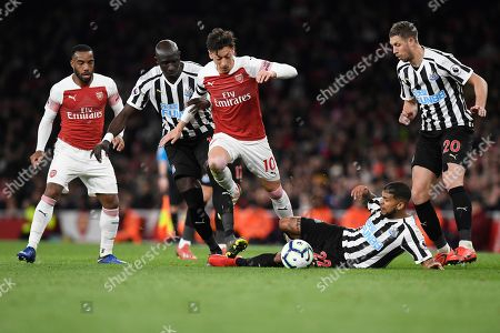 Arsenal's Mesut Ozil (C) vies for the ball against Newcastle Uniteds's DeAndre Yedlin (2-R) and Mohamed Diame (C-L) during the English Premier League soccer match between Arsenal and Newcastle United at Emirates Stadium, London, Britain, 01 April 2019.