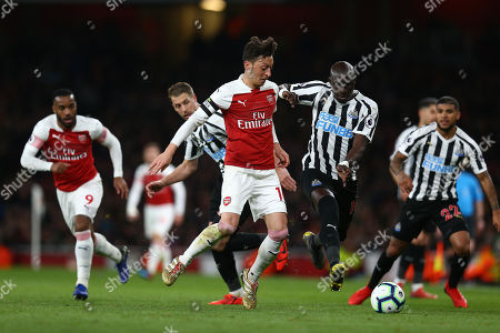 Stock Image of Mesut Ozil of Arsenal battles with  Mohamed Diame of Newcastle