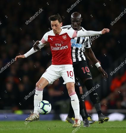 Stock Photo of Mesut Ozil of Arsenal battles with  Mohamed Diame of Newcastle