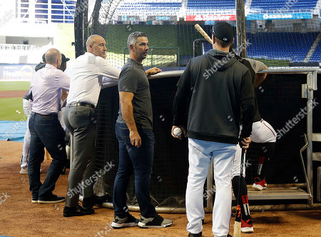 Stock Picture of Chief Executive Officer of the Miami Marlins Derek Jeter (C-L) is seen during batting practice next to former New York Yankees catcher and special advisor to baseball operations for the Marlins, Jorge Posada (C) before the start of New York Mets and Miami Marlins at Marlins Park in Miami, Florida, USA, 01 April 2019.
