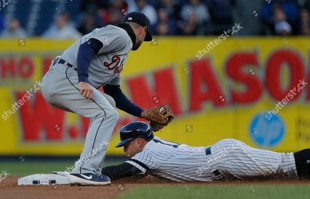 New York Yankees' Brett Gardner steals second base safely ahead of the tag from Detroit Tigers shortstop Jordy Mercer during the first inning of a baseball game, in New York