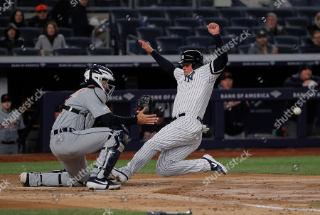 New York Yankees' Luke Voit beats the throw home to Detroit Tigers catcher Grayson Greiner to score on a hit to left field and a fielding error by Detroit Tigers left fielder Christin Stewart during the third inningof a baseball game, in New York
