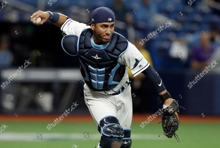 Tampa Bay Rays catcher Michael Perez fields a bunt by Colorado Rockies' Garrett Hampson during the third inning of a baseball game, in St. Petersburg, Fla. Hampson was out at first when he ran out of the runners lane