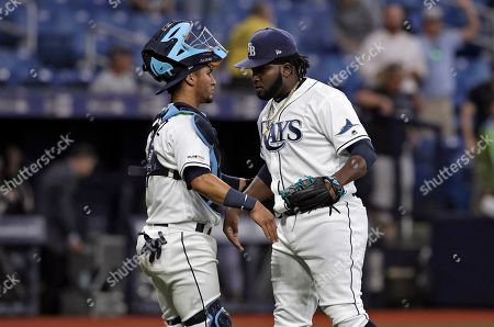 Tampa Bay Rays relief pitcher Diego Castillo, right, celebrates with catcher Michael Perez after closing out the Colorado Rockies during the ninth inning of a baseball game, in St. Petersburg, Fla